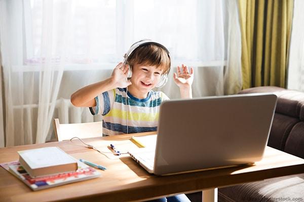 Schüler freut sich über funktionierendes Streaming der Online-Lerninhalte im Homeschooling